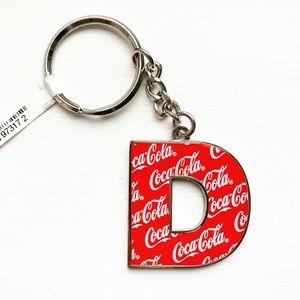 "Silver & red monogram ""D"" Coca-Cola keychain"